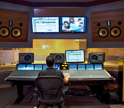 Large audio control booth A with student sitting at mixing console surrounded by three sets  of studio monitors.