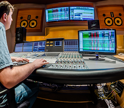Small audio control booth B, with student sitting at mixing console surrounded by two sets  of studio monitors and computer screens.