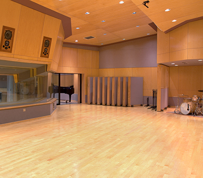 Large music recording studio A with in ceiling speakers , roll away vocal booths, grand piano and drums.