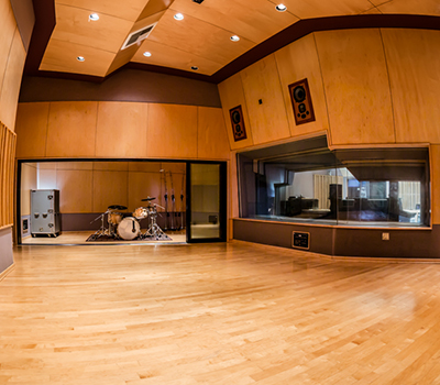Small music recording studio B with in ceiling speakers, drum and vocal booth .with view of control room.