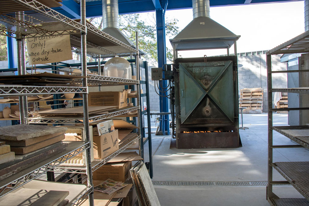 Metal shelves with stone slates and a closed kiln which has been turned on outside.