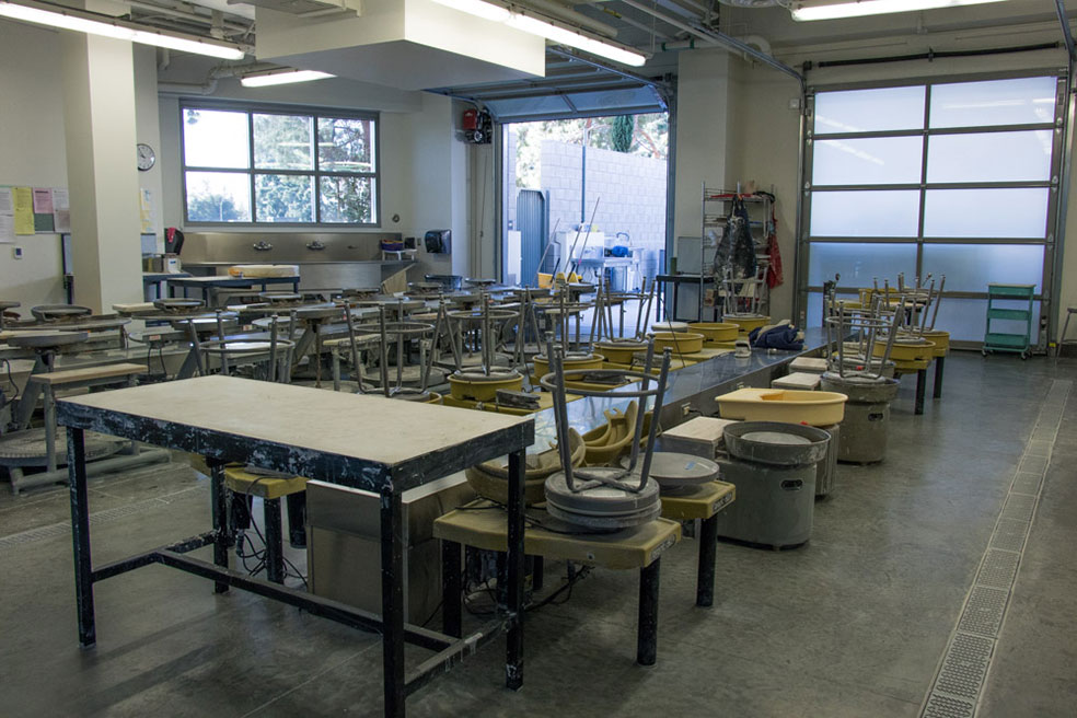 Inside the ceramic studio with stools on table and several clay potter turning wheels.