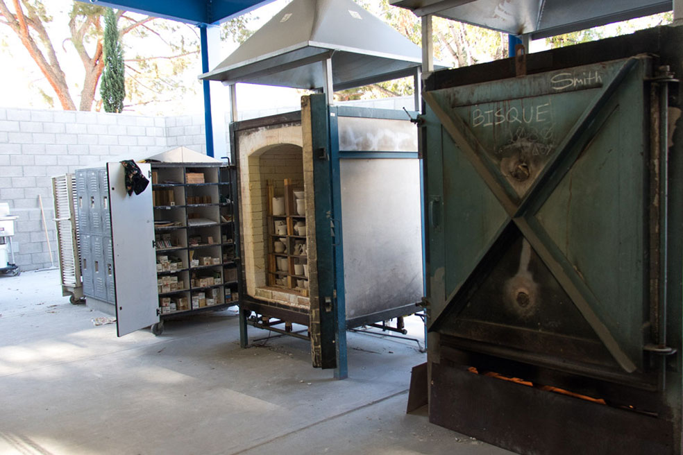 Two large ceramic kilns with ceramic pieces loaded within and ceramic storage lockers outside.