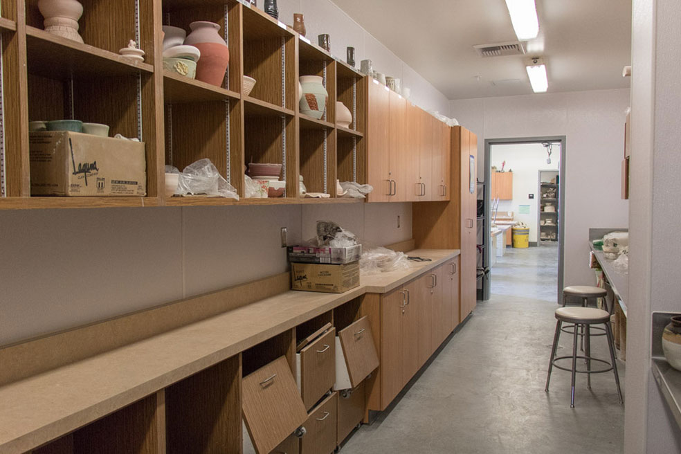Small storage room inside ceramic studio with ceramic projects on shelve on wall.