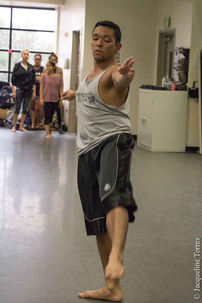 male dancer in tank top and long shorts pointing toe and fingers during class.