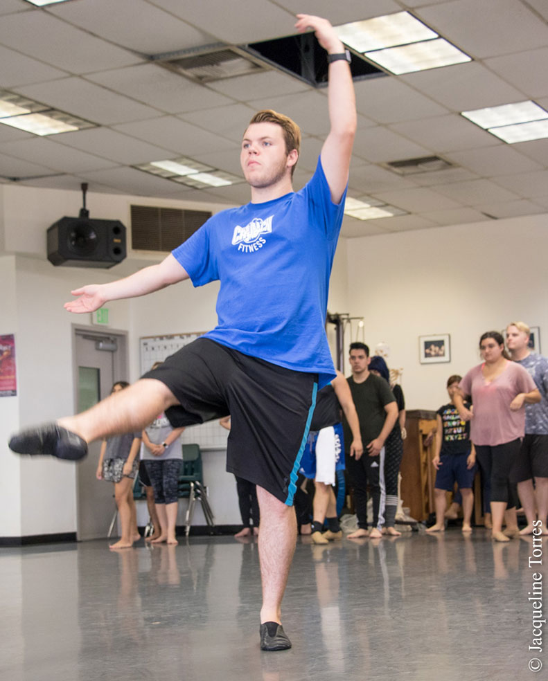 """alt=""""male dancer in blue t-shirt and long shorts pointing toe and fingers during class."""