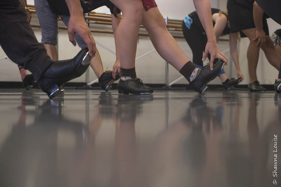 Students in tap shoes grading their shoes tips with heels down.