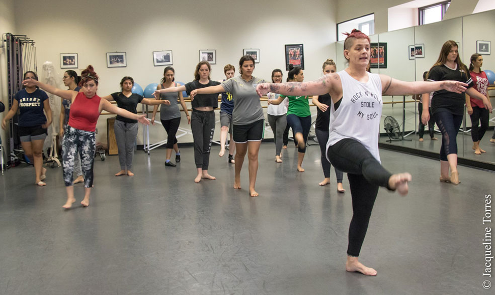 Fourteen girls in dance position taking lessons from dance instructor.