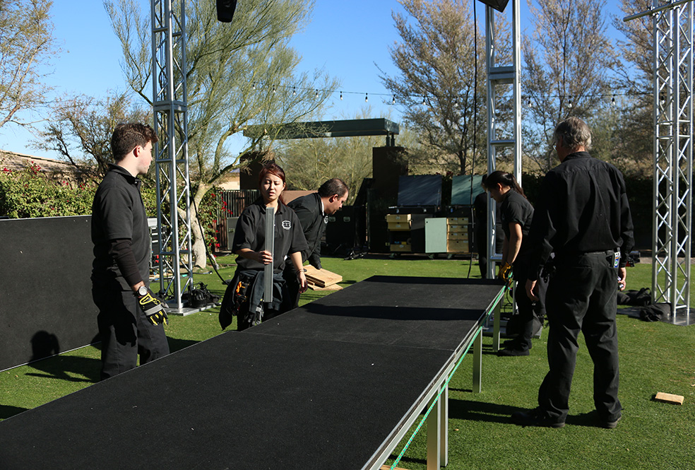 Students assembling stage for a live performance.