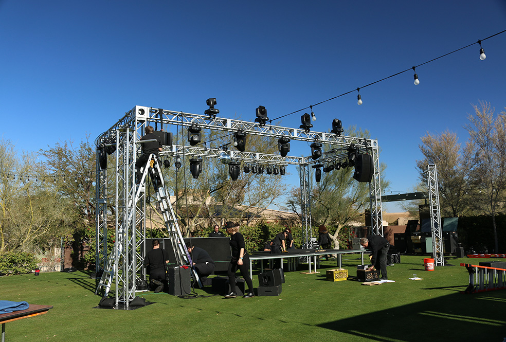 Several students building a stage and erecting large box shaped lighting truss with several stage lights installed.
