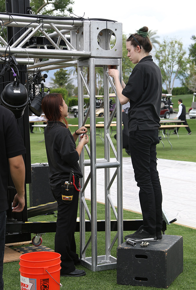 Two female ETT students assemble stage trussing for live event.