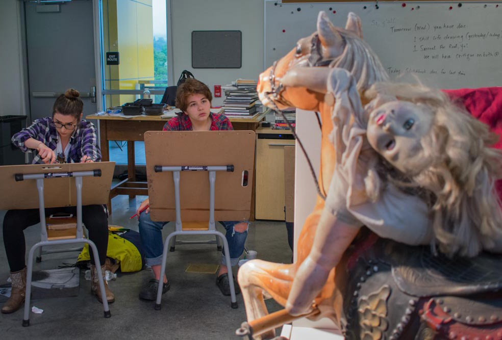 Two female students at drawing tables illustrating carousel pony with a toy doll laying on it's saddle.