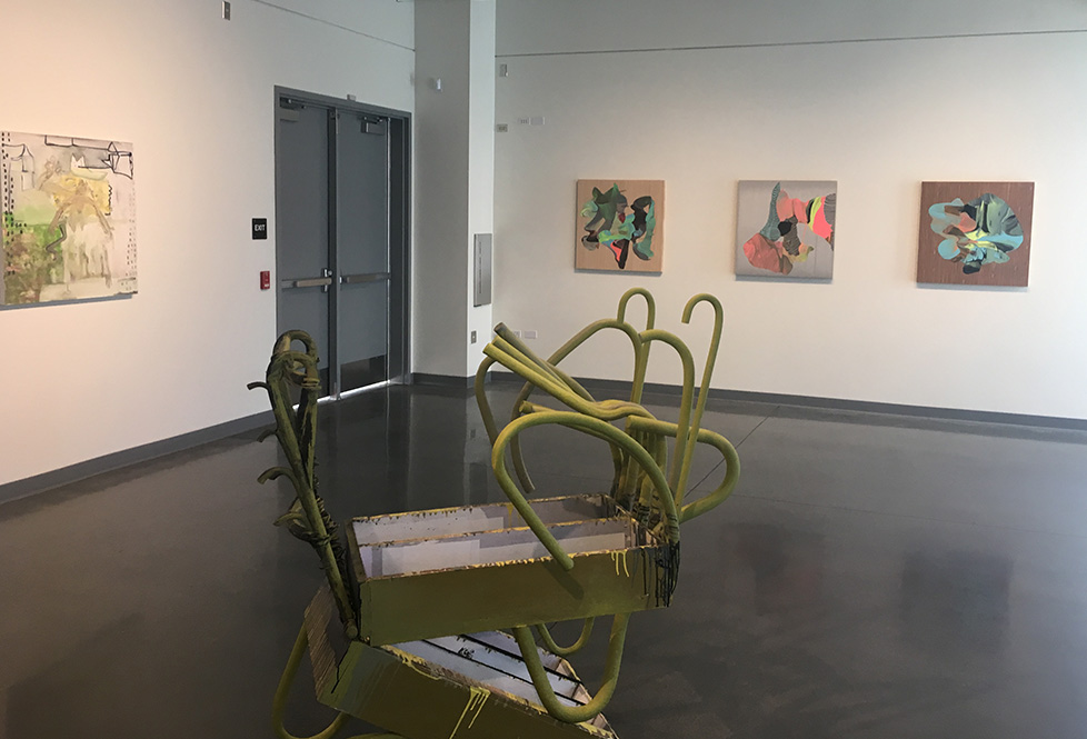 Green wooden multi-tray cart without wheels and several random handles in the center for gallery floor.