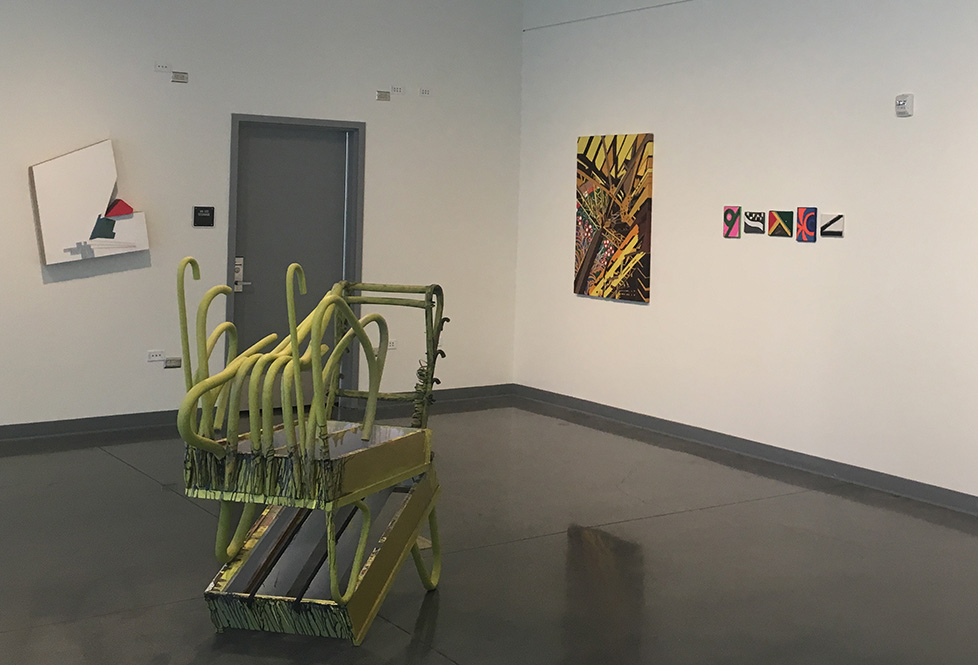 Another view of green wooden multi-tray cart without wheels and several random handles in the center for gallery floor.