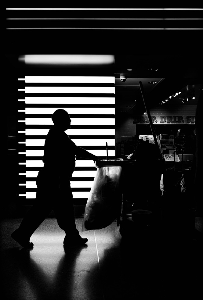 silhouette of janitor walking by open window blinds.