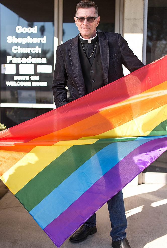 Male pastor in blue jeans and sun glasses holding a pride flag.