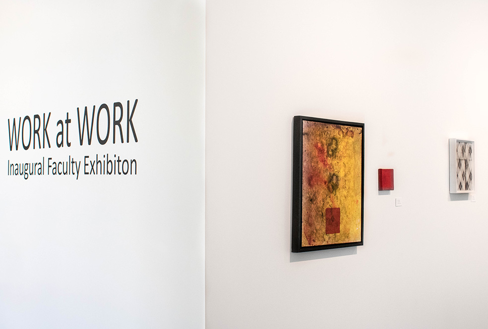 Citrus College art gallery wall with the words work to work inaugural faculty exhibition and three faculty framed exhibits.