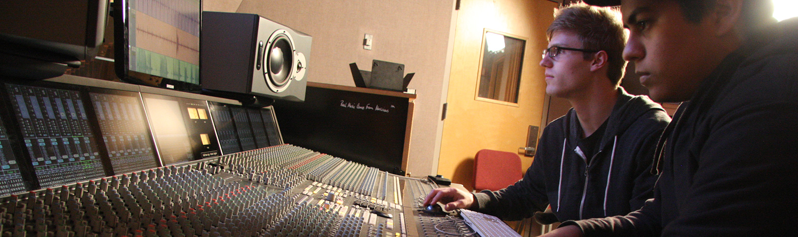 music production students sitting at studio mixing board.