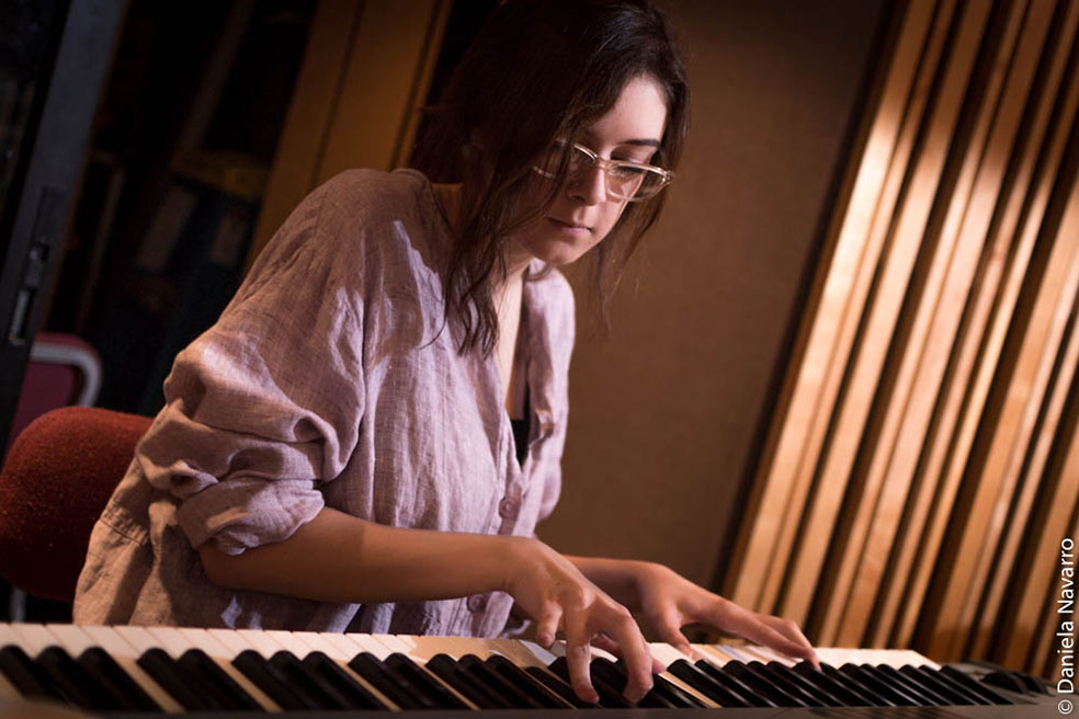 Female stunted wearing glasses playing a digital piano in studio.