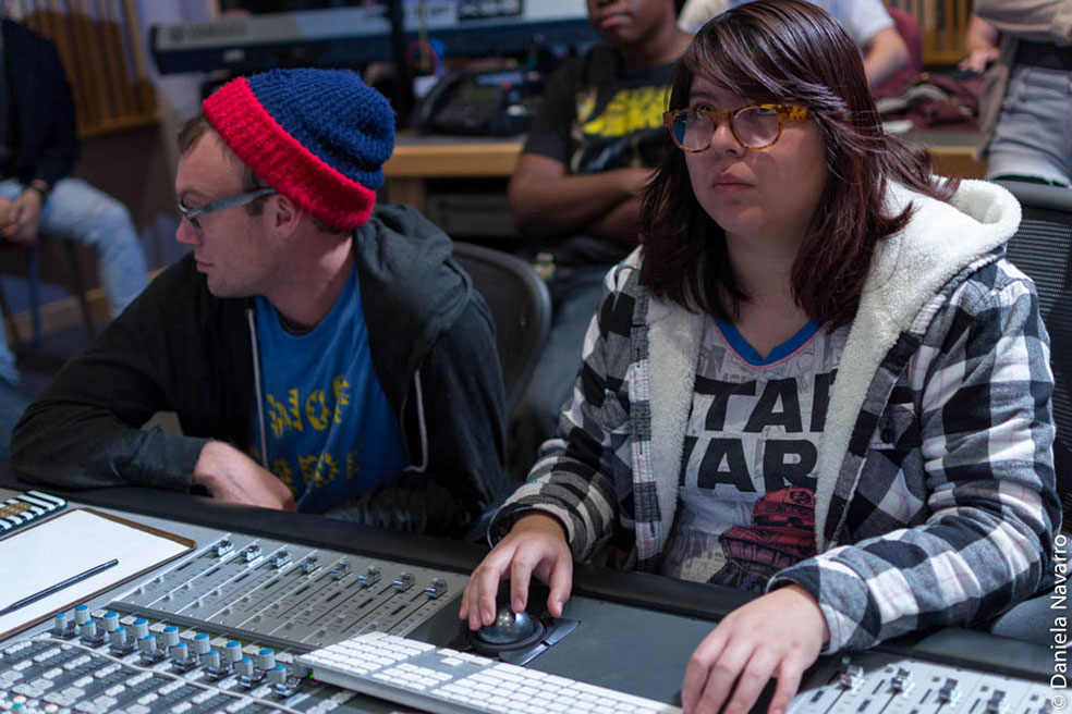 Students taking turns on mixing console during class.