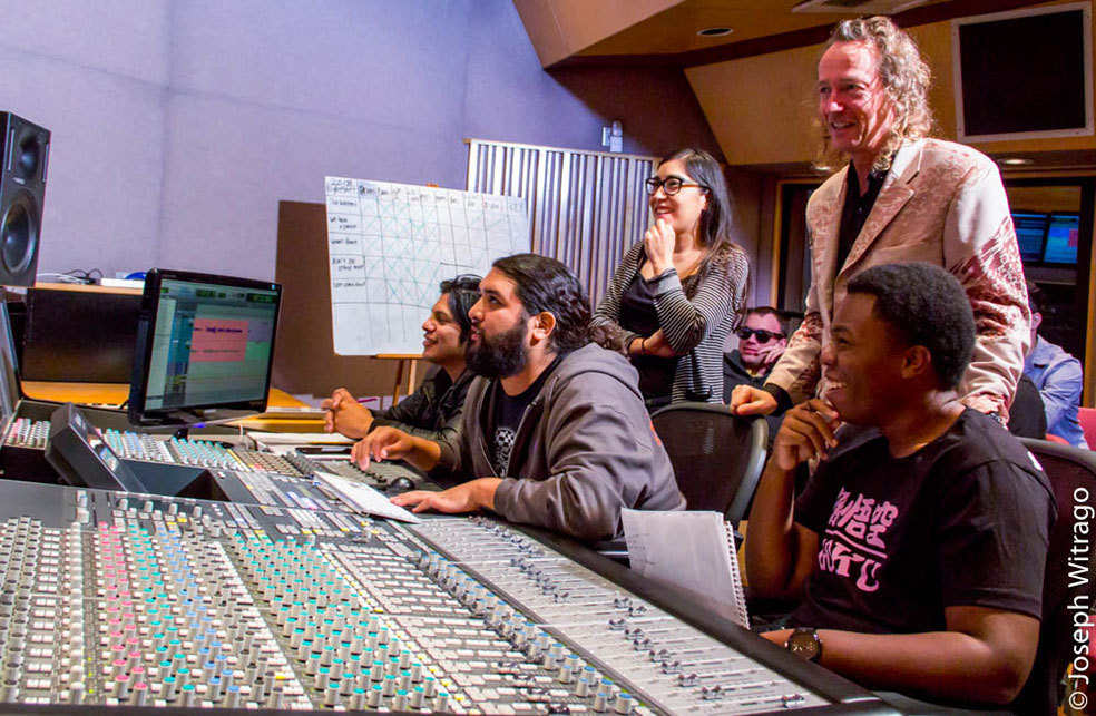 In studio class session with several students at audio mixing console with instructor  Alan Waddington looking along.