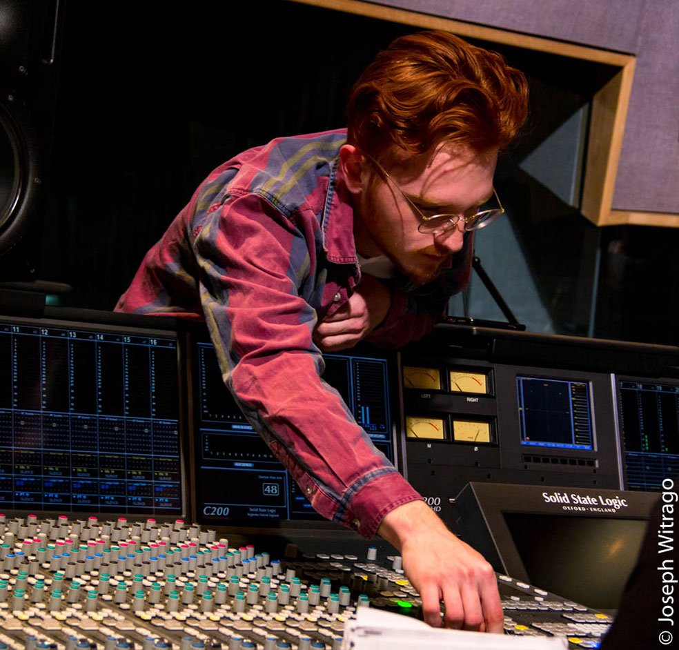 Male student reaches over audio mixing console to make adjustment to a knob.