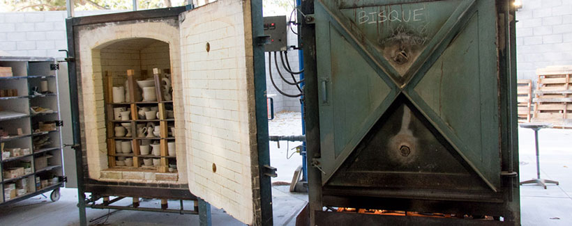 three large ceramic kilns with ceramic pieces loaded within.
