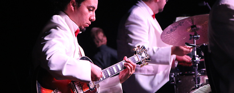 Student wearing white tuxedo and red bow tie playing a guitar as a member of  Blue Note Orchestra at a live event.