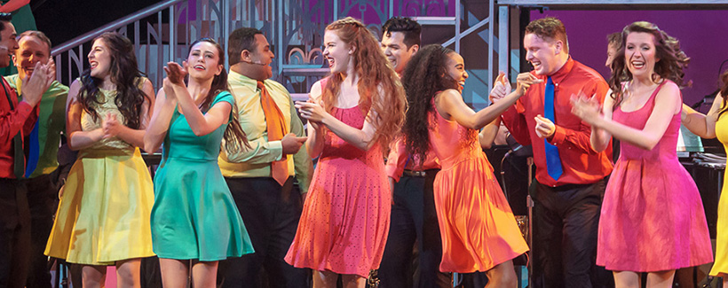 Several students wearing very colorful outfits while dancing, clapping and singing in a ,musical theater performance.